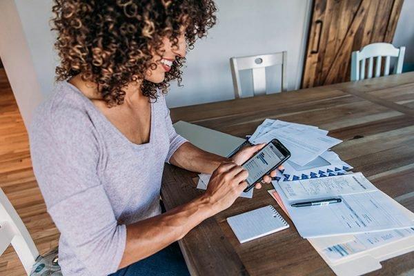 Investidora negra com cabelos cacheados mexendo no celular para descobrir qual perfil de investidor mais se adequa a si