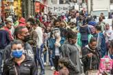 Mulher usando máscara protetora e protetor facial fala ao telefone enquanto as pessoas caminham em uma popular rua comercial em meio ao surto da doença coronavírus (COVID-19), em São Paulo, Brasil, em 15 de julho de 2020. Foto tirada em 15 de julho , 2020. REUTERS / Amanda Perobelli