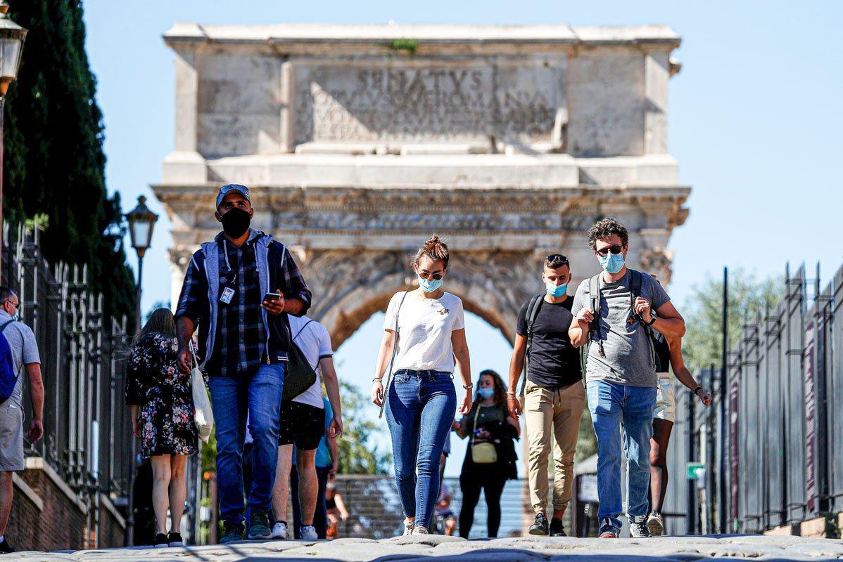 Pessoas usando máscaras faciais de proteção caminham perto do Coliseu enquanto as autoridades locais na capital italiana Roma ordenaram que coberturas faciais fossem usadas em todos os momentos ao ar livre, em um esforço para conter a propagação da doença coronavírus (COVID-19), em Roma, Itália, 8 de outubro de 2020. REUTERS / Guglielmo Mangiapane