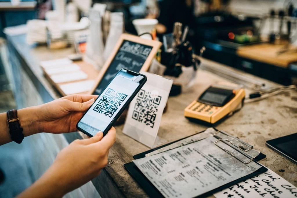 Cliente digitalizando o código QR, fazendo um pagamento sem contato rápido e fácil com seu smartphone em um café