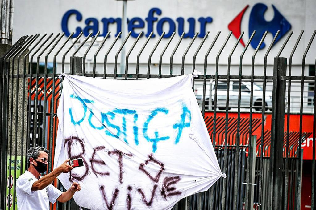 Homem tira foto em frente a faixa de protesto contra a morte de João Alberto Silveira Freitas, morto por espancamento por seguranças em loja do Carrefour em Porto Alegre