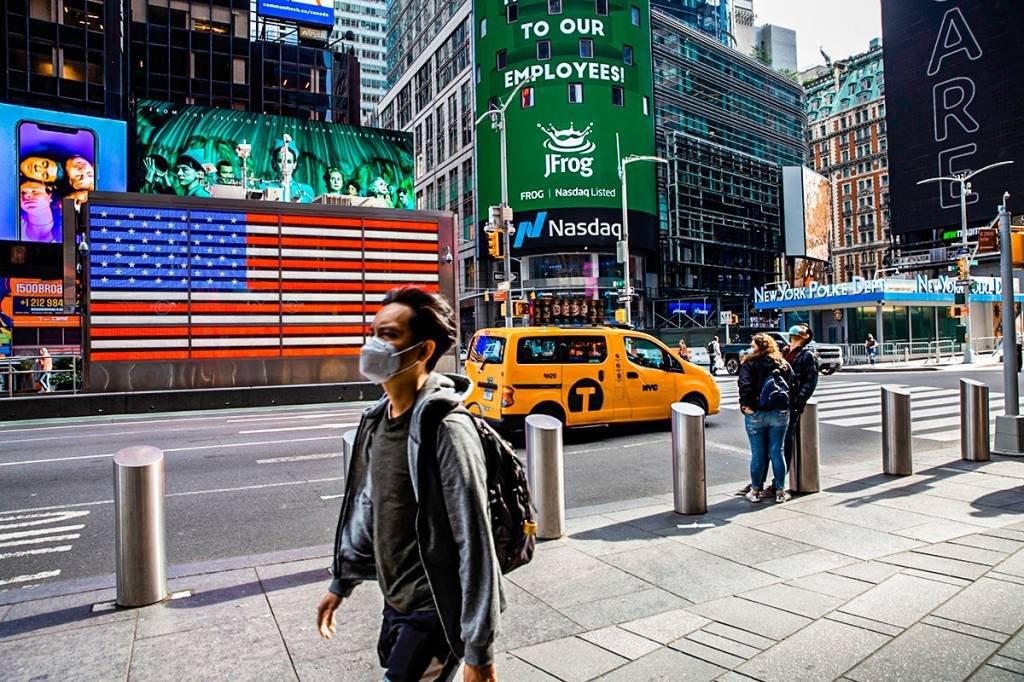 Pedestres usando máscaras de proteção passam pelo Nasdaq MarketSite em Nova York, EUA, na sexta-feira, 2 de outubro de 2020.