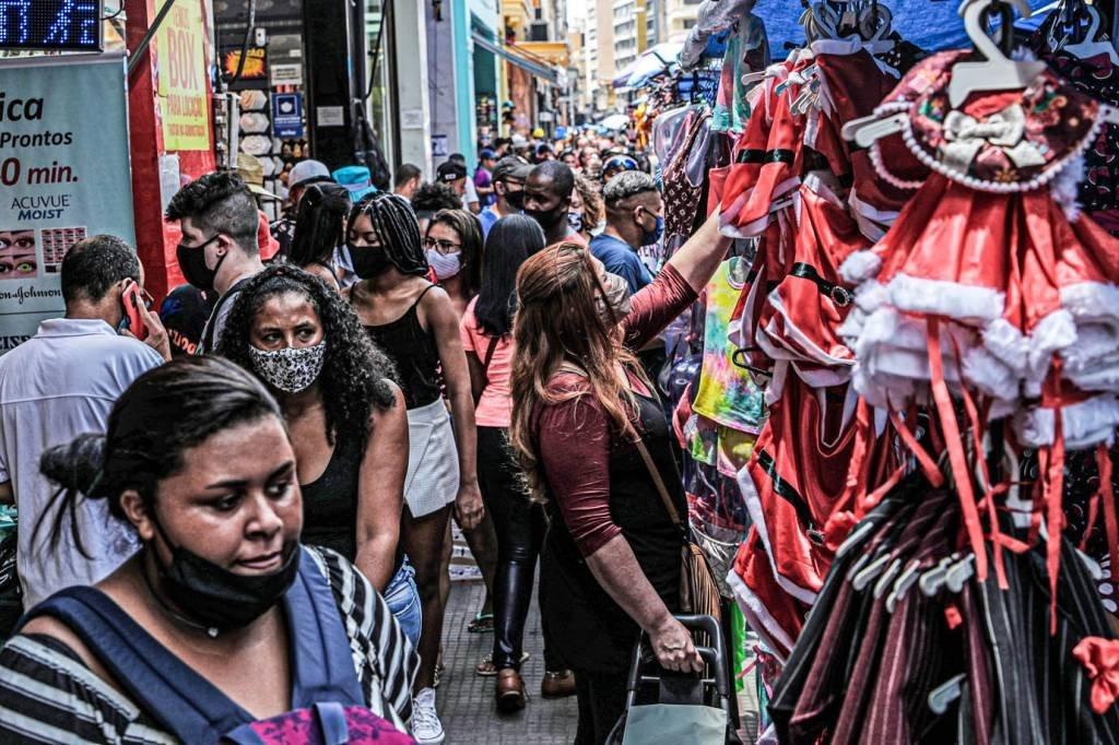 Mulher olha para roupas enquanto as pessoas caminham na popular rua comercial 25 de Março antes do Natal, em meio ao surto da doença do coronavírus (COVID-19), no centro de São Paulo, Brasil, 21 de dezembro de 2020. REUTERS / Amanda Perobelli
