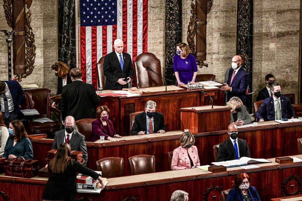 A presidente da Câmara dos EUA, Nancy Pelosi, ouve o vice-presidente dos EUA, Mike Pence, falar durante uma sessão conjunta do Congresso para certificar os resultados das eleições de 2020 no Capitólio em Washington, EUA, 6 de janeiro de 2021. Erin Scott / Pool via REUTERS