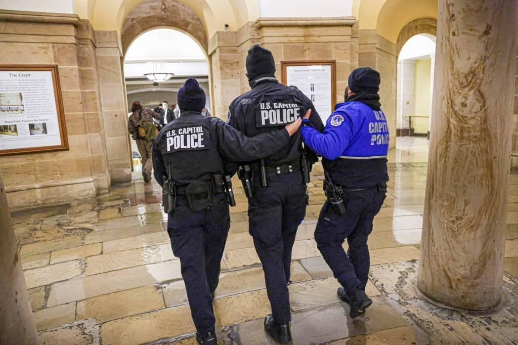 Membros da Polícia do Capitólio dos EUA caminham dentro do Capitólio enquanto apoiadores do protesto do presidente dos EUA, Donald Trump, do lado de fora, em Washington, EUA, 6 de janeiro de 2021. REUTERS / Jonathan Ernst