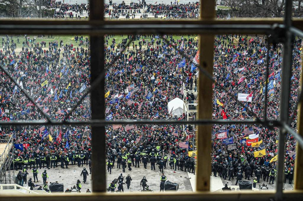 A polícia segura os apoiadores do presidente dos EUA, Donald Trump, enquanto eles se reúnem em frente à Rotunda do Capitólio dos EUA em 6 de janeiro de 2021, em Washington, DC. - Os manifestantes violaram a segurança e entraram no Capitólio enquanto o Congresso debatia a Certificação de Voto Eleitoral da eleição presidencial de 2020. (Foto de Olivier DOULIERY / AFP) (Foto de OLIVIER DOULIERY / AFP via Getty Images)