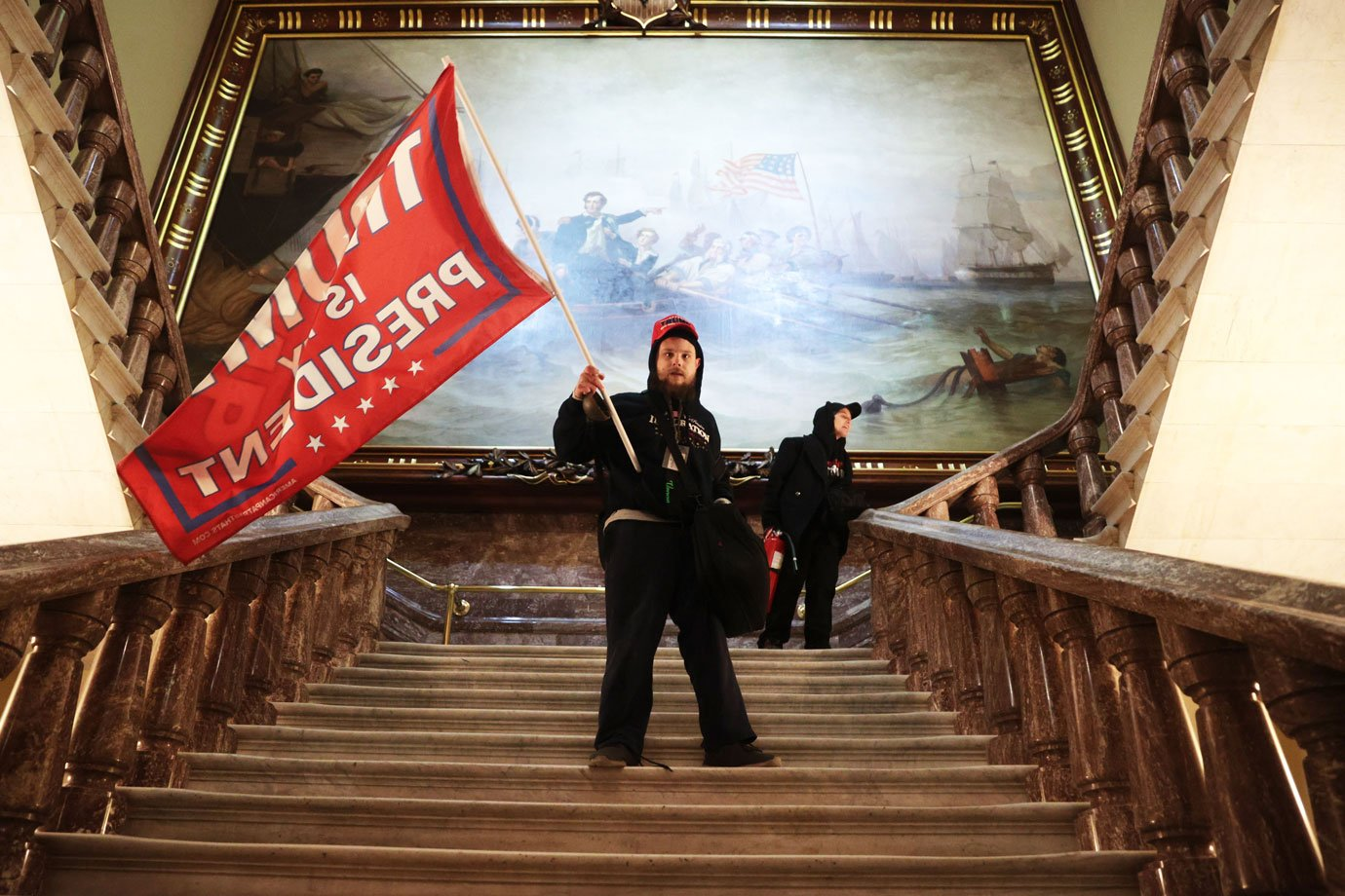 Um manifestante segura uma bandeira Trump dentro do edifício do Congresso dos EUA perto da Câmara do Senado em 06 de janeiro de 2021 em Washington, DC. O Congresso realizou uma sessão conjunta hoje para ratificar a vitória do Colégio Eleitoral do presidente eleito Joe Biden sobre o presidente Donald Trump.