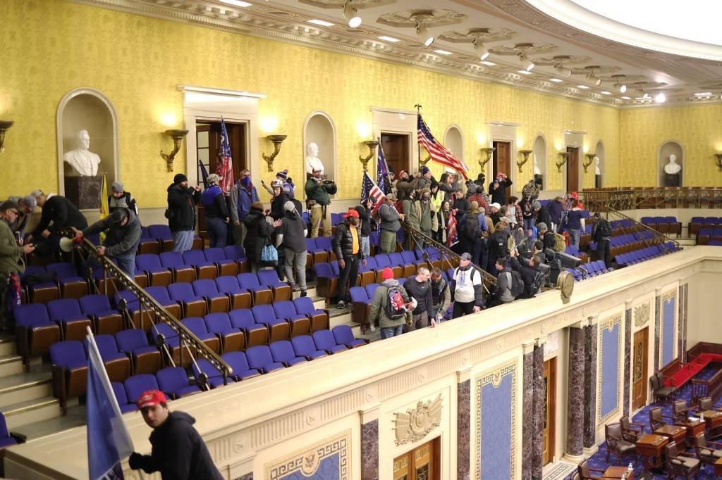 Os manifestantes entram na Câmara do Senado em 06 de janeiro de 2021 em Washington, DC. O Congresso realizou uma sessão conjunta hoje para ratificar a vitória do Colégio Eleitoral 306-232 do presidente eleito Joe Biden sobre o presidente Donald Trump. Manifestantes pró-Trump entraram no edifício do Capitólio dos EUA após manifestações em massa na capital do país