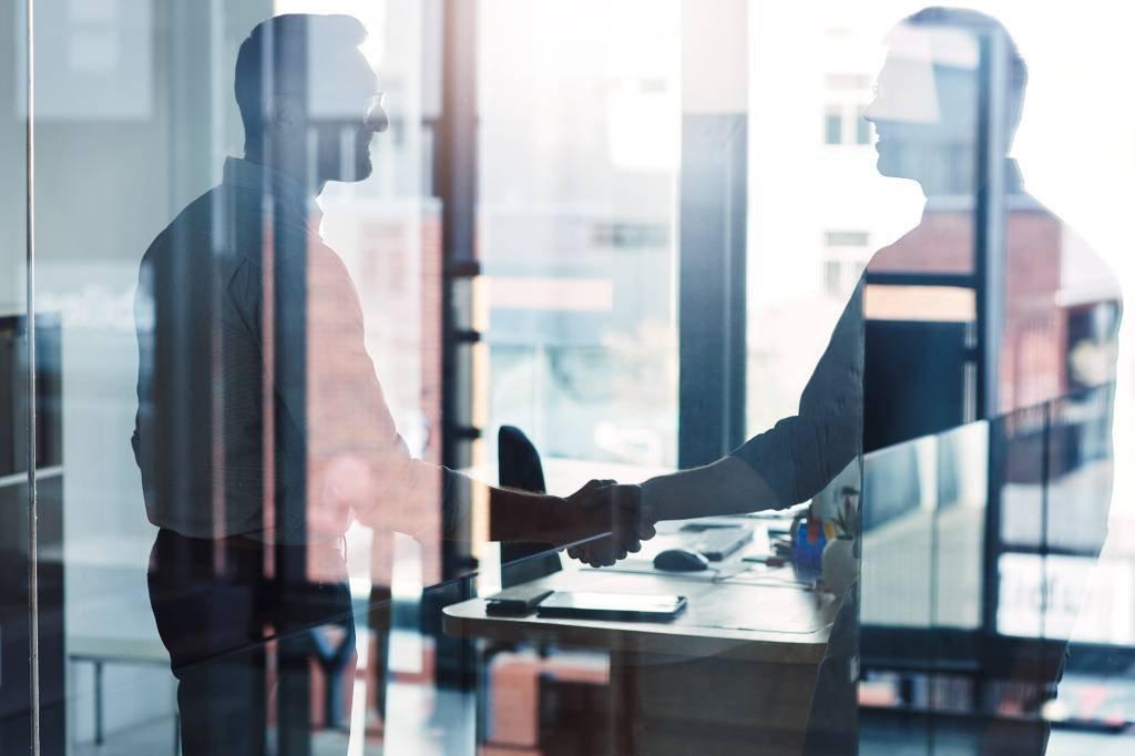 Foto de dois empresários apertando as mãos em um escritório