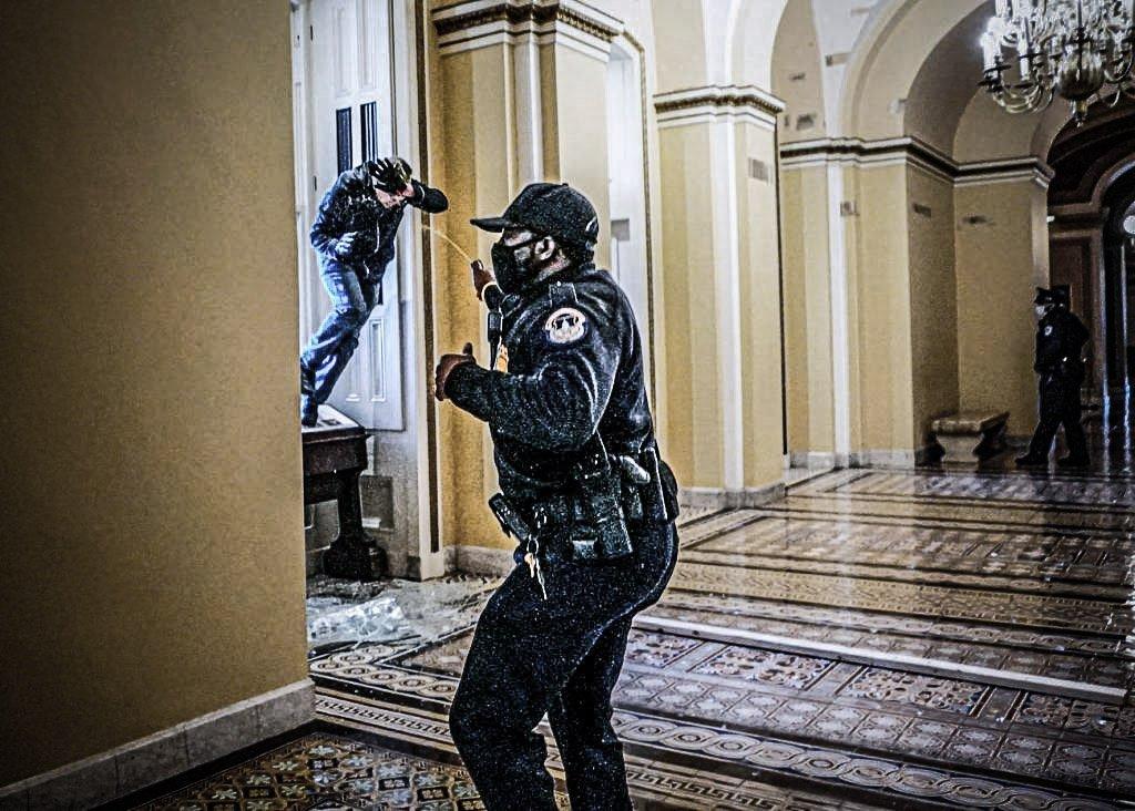Um policial do Capitólio dos EUA atira spray de pimenta em um manifestante que tentava entrar no prédio do Capitólio durante uma sessão conjunta do Congresso para certificar os resultados da eleição de 2020 no Capitólio em Washington, EUA, 6 de janeiro de 2021. Kevin Dietsch / Pool via REUTERS