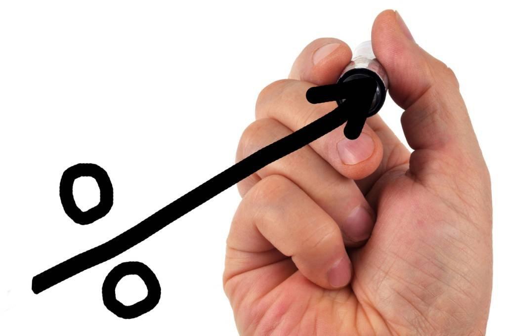 Mão desenhando um sinal de porcentagem mostrando crescimento