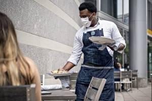 Funcionário de um restaurante usando máscara protetora entrega pedido a clientes em Washington, DC, EUA, na sexta-feira, 29 de maio de 2020.