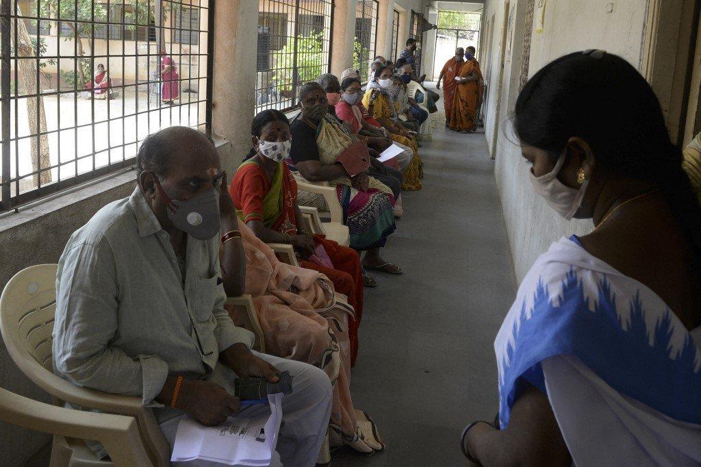 Idosos aguardam sua vez de receber a dose da vacina de Covishield contra o coronavírus Covid-19 em uma escola secundária do governo em Hyderabad em 5 de abril de 2021