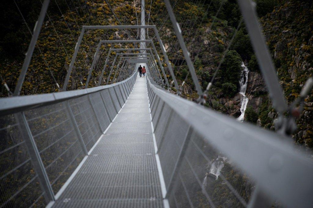 Pessoas a atravessar pela primeira vez a Ponte de Arouca 516, a maior ponte pedonal suspensa do mundo, em Arouca, norte de Portugal, a 29 de abril de 2021