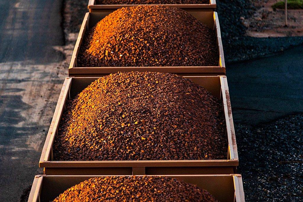 Um trem de carga transportando minério de ferro viaja para Port Hedland, Austrália, na terça-feira, 19 de março de 2019. A dois dias de carro da cidade grande mais próxima, Perth, Port Hedland é o nexo da indústria de minério de ferro da Austrália, o terminal de uma das ferrovias privadas mais longas da Austrália que transporta minério cerca de 400 quilômetros (250 milhas) das minas do BHP Group e Fortescue Metals Group Ltd. A linha operou um trem de teste recorde pesando quase 100.000 toneladas que era mais de 7 quilômetros em 2001, e mesmo trens normais transportam até 250 vagões de minério.