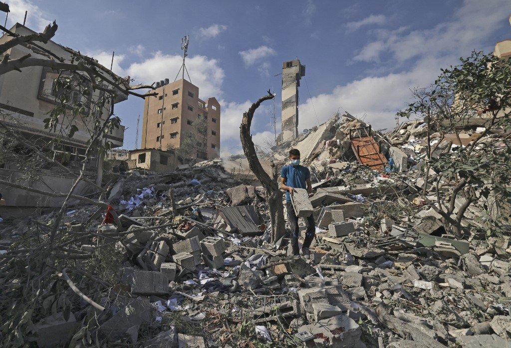 Conflito Israel-Gaza: jovem palestino procura itens recuperáveis em meio aos escombros do prédio Kuhail, que foi destruído em um ataque aéreo israelense na cidade de Gaza em 18 de maio de 2021.