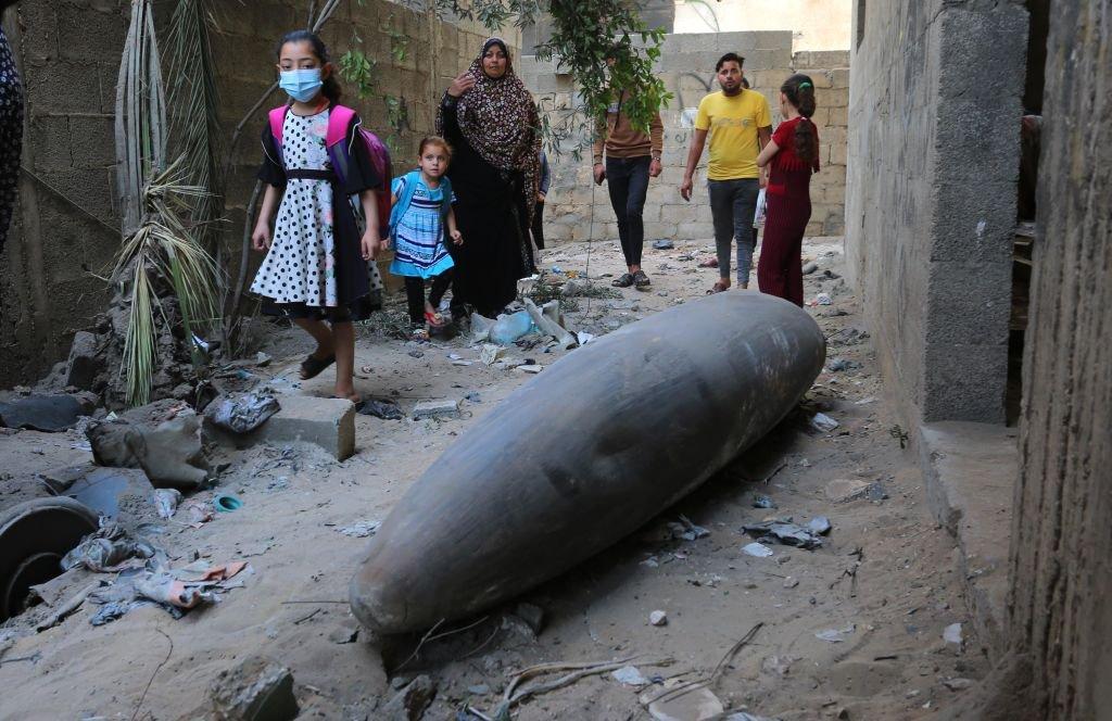 Conflito Israel-Palestina: pessoas olham para um míssil não detonado lançado por Israel no bairro de al-Rimal enquanto aviões de guerra israelenses continuam a realizar ataques aéreos na cidade de Gaza, Gaza em 18 de maio de 2021.