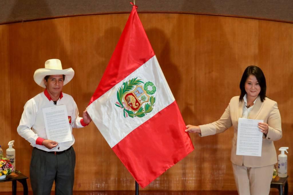 Lado a lado, os candidatos Pedro Castillo (homem, com chapéu e camisa) e Keiko Fujimori (mulher, de terno) seguram bandeira do Peru e posam para foto com um documento em mãos