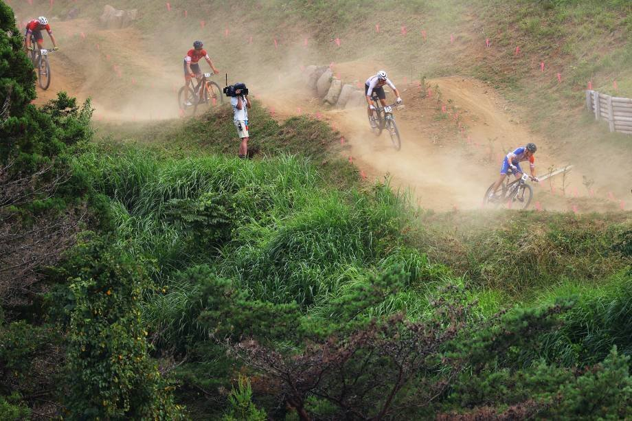 IZU, JAPAN - JULY 26: (LR) A general view of Martin Fedore Kossmann of Team Chile, Maximilian Vodel of Team Austria, Maximilian Brandl of Team Germany and Jordan Sarro of Team France wander through the dust during the men's cross-country race on Day Three of the 2020 Tokyo Olympics at the Olympic Stadium Izu Mountain Bikes on July 26, 2021 in Izu, Shizuoka, Japan.  (Photo by Tim De Wiley/Getty Images)