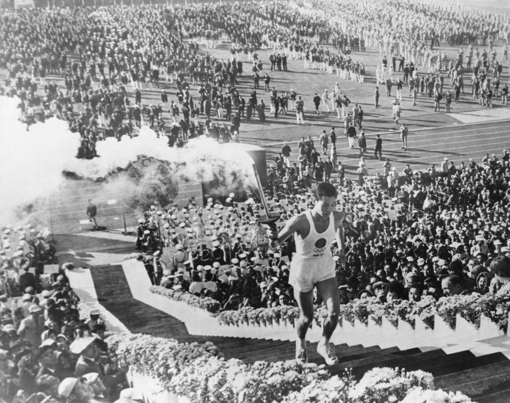 """Yoshinori Sakai, o """"bebê de Hiroshima"""": nascido em Hiroshima no dia da bomba atômica, o atleta foi escolhido para ascender a pira olímpica 19 anos depois e simbolizar a reconstrução do país"""