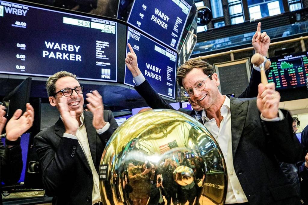 Os fundadores e co-CEOs Neil Blumenthal (à esq.) e Dave Gilboa, da Warby Parker, tocam o sino para a estreia na Bolsa de Nova York | Foto: Brendan McDermid/Reuters