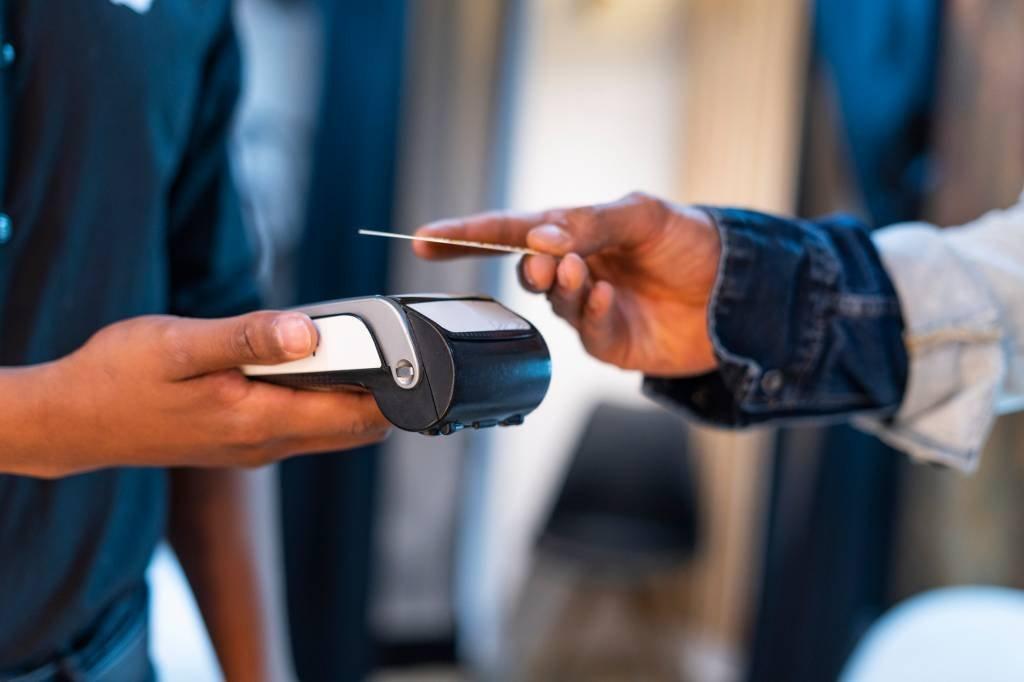 Um funcionário da loja estende a mão para o cliente pagar por meio de cartão