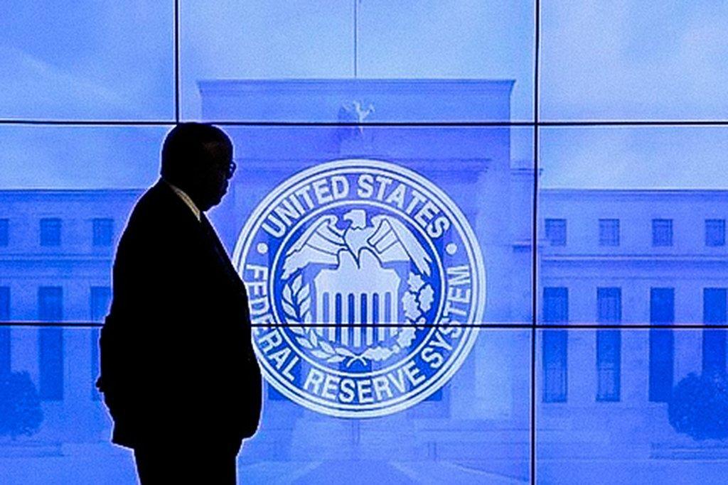 Homem passa por logo do Federal Reserve em Washington, Estados Unidos